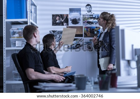 Horizontal view of police officers searching files - stock photo