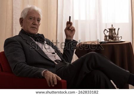 Horizontal view of senior millionaire smoking cigar - stock photo