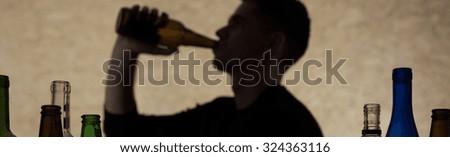 Horizontal view of teenage boy drinking beer - stock photo