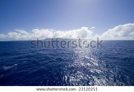 Horizontal view of the blue tropical ocean with the island of kauai in the distance.