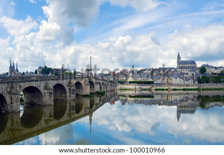 Horizontal view of the bridge on the river Loire in France. Across the sky a large number of very beautiful clouds with a beautiful reflection on the water - stock photo