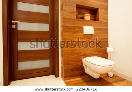 Horizontal view of toilet in wooden bathroom - stock photo