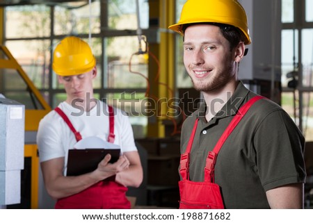Horizontal view of two specialists working at factory - stock photo