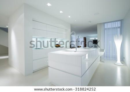Horizontal view of white gleaming kitchen interior - stock photo