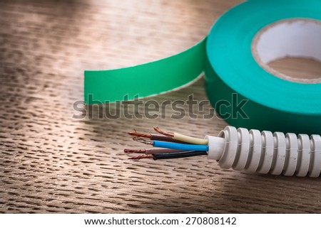 horizontal view roll of green insulating tape and electric cable in corrugated pipe  - stock photo