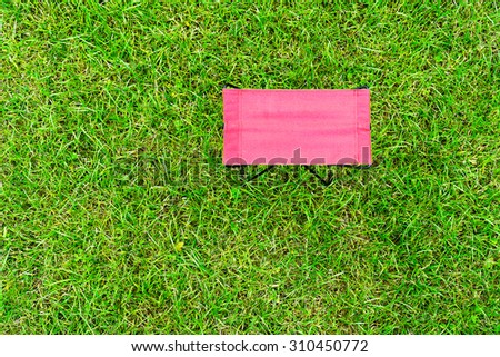 Horizontal vivid red chair view from above on green grass background