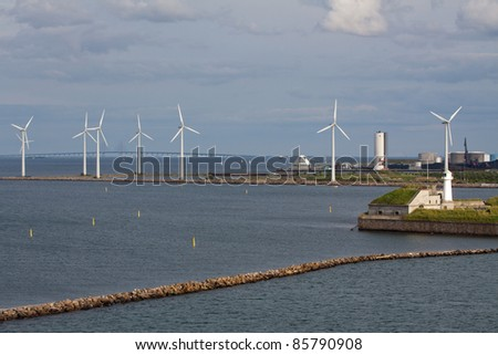 horizontal wind turbine generators and breakwater - stock photo
