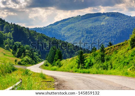 horizontal winding old road stretches into the distance in the mountains under a cloudy evening summer sky - stock photo