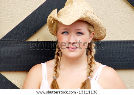 Horizontally framed outdoor shot of a smiling teenage girl, with blond hair and blue eyes, standing next to barn door wearing a straw cowboy hat. - stock photo