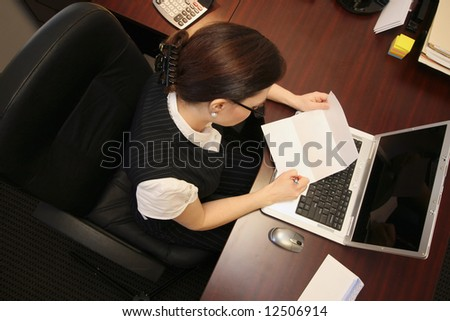 Horizontally framed overhead shot of a businesswoman at her desk reading a letter - stock photo
