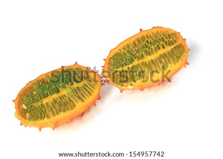 Horned melon (Cucumis metuliferus) in longitudinal section, isolated against a white background - stock photo