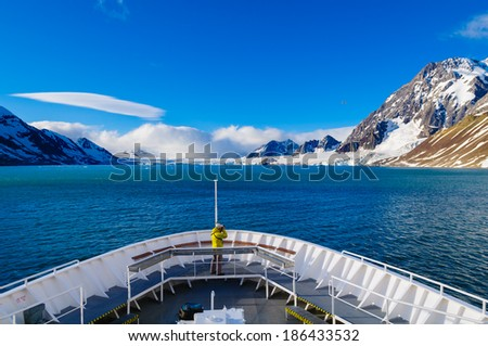 HORNSUND, SVALBARD,NORWAY - JULY 26, 2010:  Photographer on the bow of the National Geographic Explorer cruise ship in the Arctic. - stock photo