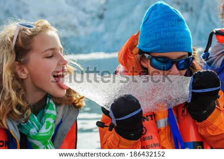 HORNSUND, SVALBARD,NORWAY - JULY 26, 2010: Young girls from the National Geographic Explorer cruise ship playing with salt water ice from the Arctic Ocean. - stock photo
