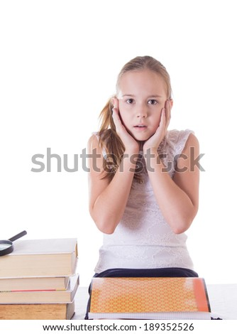 Horrified schoolgirl with pile of books isolated on white - stock photo