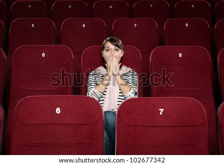 Horrified woman in the movie theater - stock photo