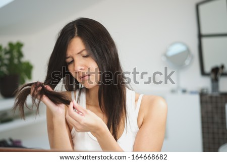 Horrified young woman looking in the bathroom mirror staring open mouthed at the first grey hair on her scalp, a first sign of aging, or noticing that she is suffering from dandruff - stock photo
