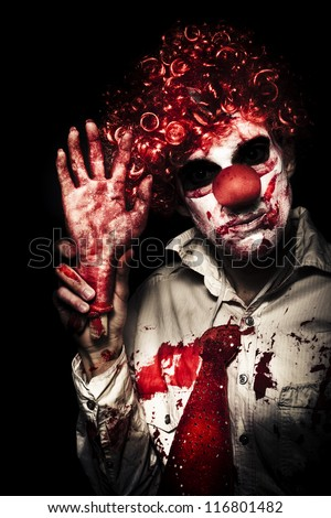 Horror Clown Waving Chopped Off Hand To Welcome You To A Evil Circus Act Of Terror On Black Background - stock photo
