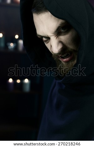 Horror male vampire hungry with candles in background - stock photo