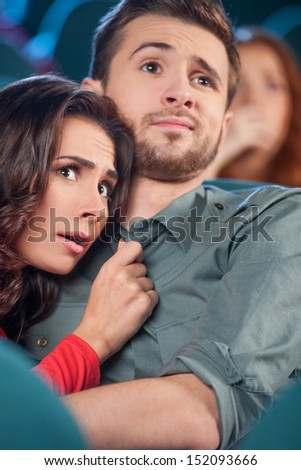 Horror movie. Terrified young couple hugging while watching movie the cinema