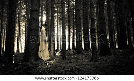 Horror scene - mysterious woman in the forest - stock photo