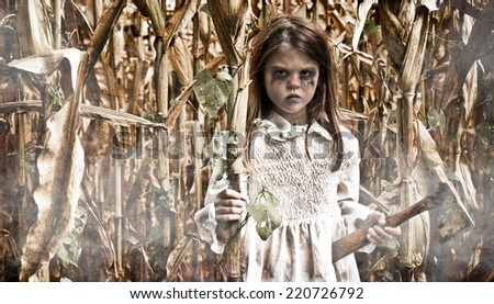 Horror scene of a Girl in a Corn Field holding a Hatchet - stock photo