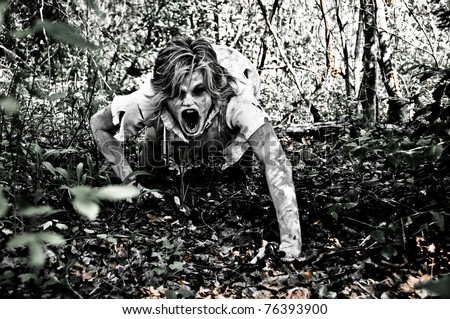 Horror Scene of a Possessed Woman Crawling and Screaming through Woods - stock photo
