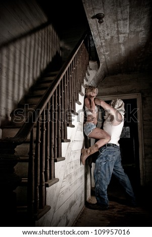 Horror scene of a woman being held off the ground and choked by hooded man. - stock photo