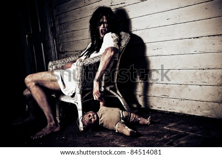 Horror Scene of a Woman Possessed holding a doll sitting in a chair - stock photo
