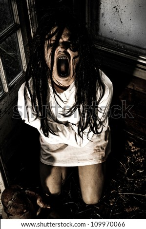 Horror Scene of a Woman Possessed Wearing a Straight Jacket Screaming - stock photo
