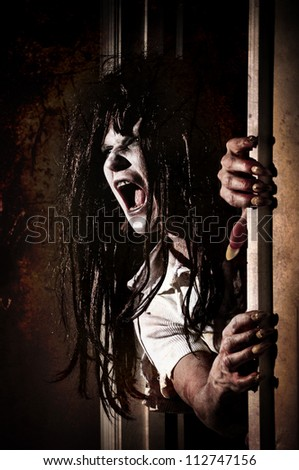 Horror Scene of a Zombie or Woman Possessed Coming out of a door - stock photo