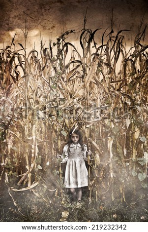 Horror Scene with scary little girl in a corn field - stock photo
