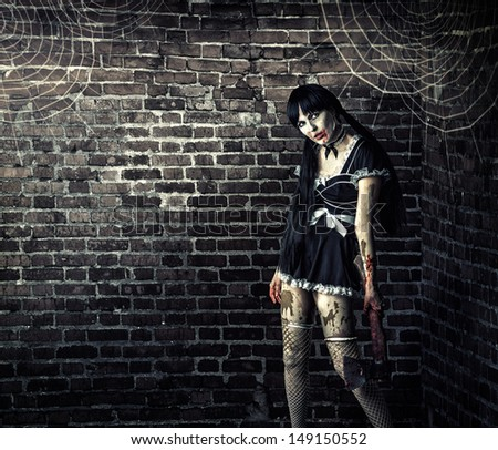 Horror. Sexy dirty woman zombie  holding a bloody ax  - stock photo
