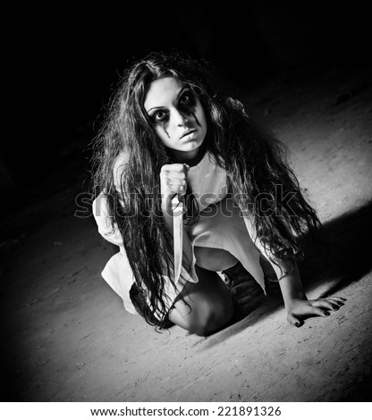 Horror shot: a scary monster girl with knife in hands. Black and white - stock photo