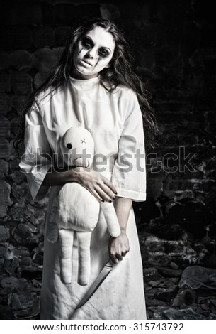 Horror shot: a scary monster girl with moppet doll and knife in hands - stock photo
