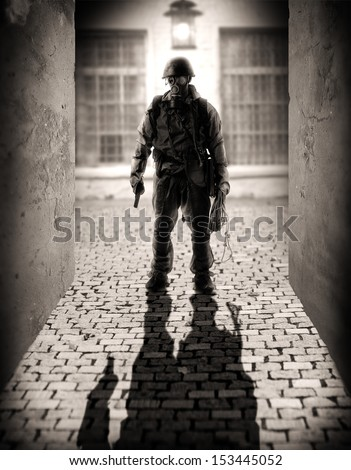 Horror. silhouette of a dangerous military men holding hand gun in the alley by the light of a lantern at night - stock photo