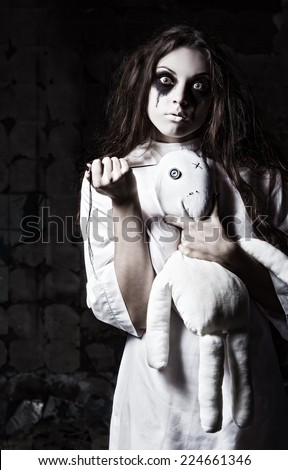 Horror style shot: a strange crazy girl with moppet doll and needle in hands - stock photo