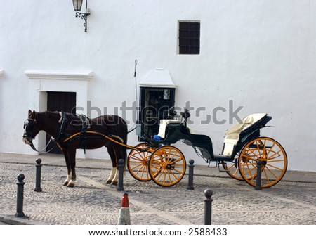 Horse and carriage in Ronda Spain on cobble stone street against white wall - stock photo