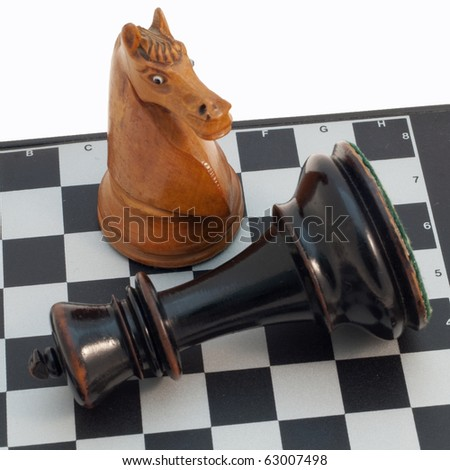 Horse and king on a chess board, isolated on white - stock photo
