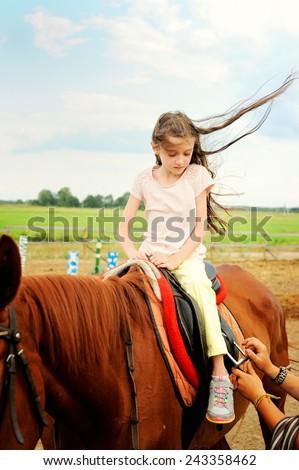 Horse and lovely brunette kid girl on the beauty summer day  - stock photo