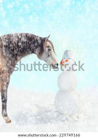 Horse and snowman in snow - stock photo
