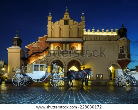 Horse carriage parked in front of Gothic Cloth Hall Sukiennice on the Main Market Square in Krakow by night - stock photo