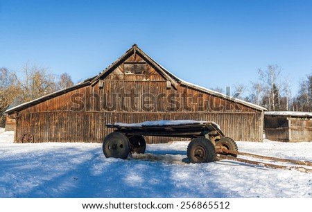 Horse carriage with car wheels and shafts that lie ahead in the snow, on a background rural wooden barn. Tomcats lie on the projections of the barn and bask in the bright low winter-spring sun - stock photo