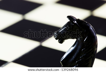 Horse( chess piece) with a chess table in background - stock photo