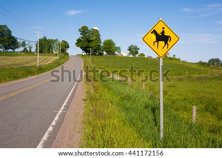Horse crossing sign on rural road. - stock photo