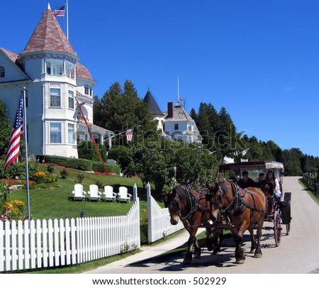 Horse-drawn carriage and cottage on Mackinac Island, Michigan - stock photo
