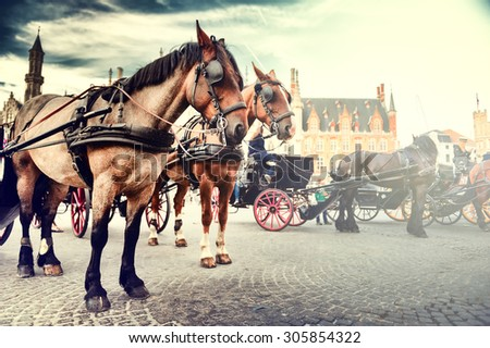 Horse-drawn carriages on the Old Market square (Grote markt). Bruges, Belgium - stock photo