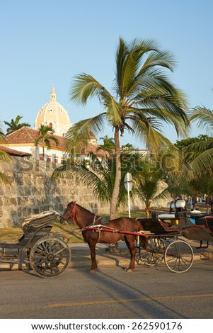 Horse drawn carriages used by tourists waiting alongside the fortified walls of the historic Spanish colonial city of Cartagena de Indias in Colombia - stock photo