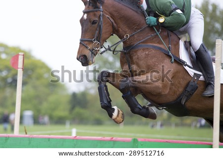 Horse Jumping over a fence at an event - stock photo