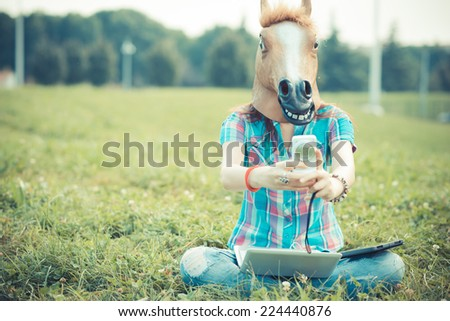 horse mask unreal hipster woman using technology in the park - stock photo