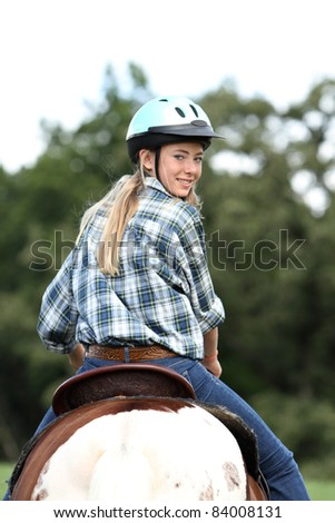horse rider looking back over shoulder - stock photo